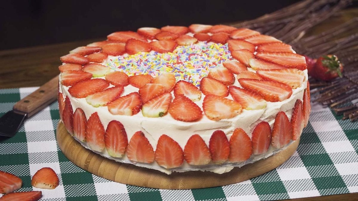 Strawberry Cream Cake Recipe, A soft sponge cake brushed with red wine, with buttercream frosting, then topped with sliced fresh strawberries..