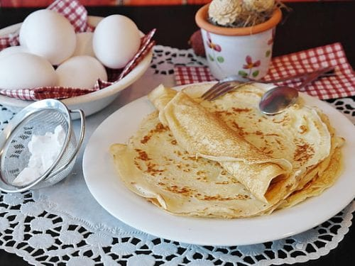 crepes on a white plate surrounded by eggs and a sieve with flour in it