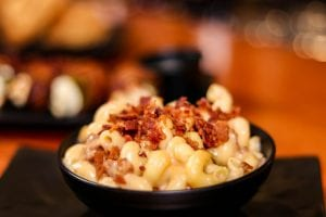 mac and cheese with bacon bits sprinkled on top in a black bowl