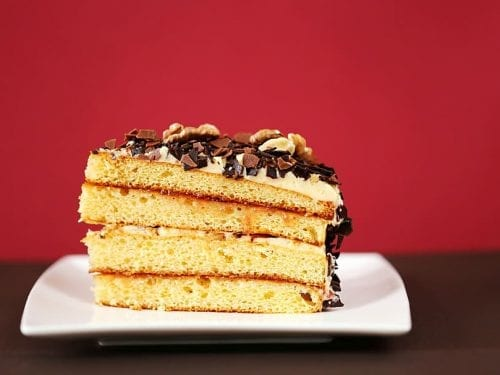 a slice of a 4-layer cake with frosting