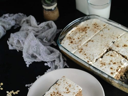 applesauce cake covered in white frosting and cinnamon powder
