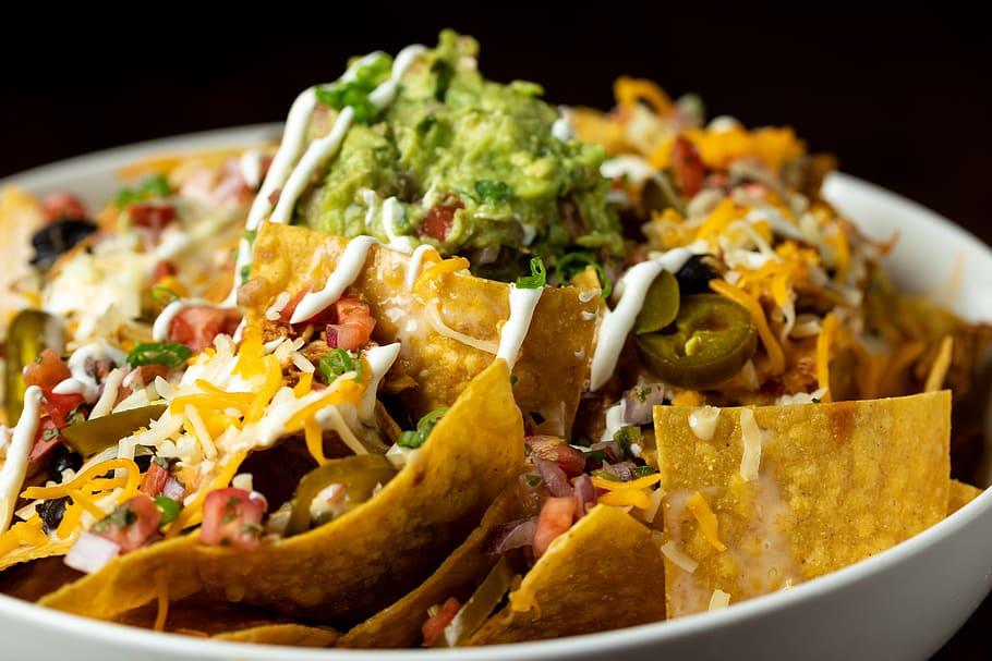 a bowl of fajita nachos in a white bowl