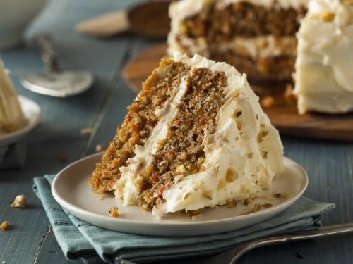 a slice of two-layered carrot cake covered in icing, with the full cake in the background