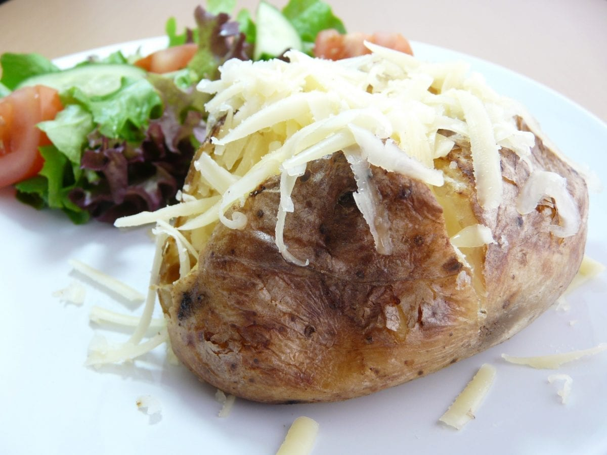 jacket potato topped with cheese and salad on the side