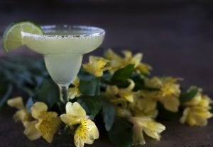 margarita in a glass surrounded by yellow flowers