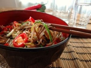 soba noodles mixed with vegetables and cut chilli peppers in a bowl