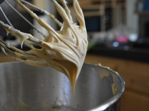 frosting or icing dripping from a whisk into a bowl