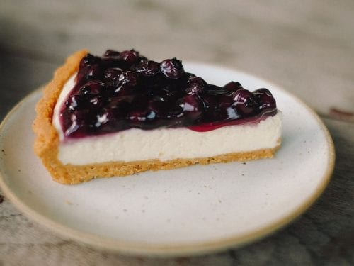 a slice of cheesecake pie topped with blueberry filling