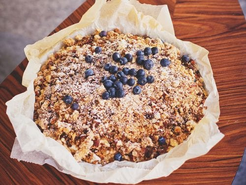 blueberry crumble pie topped with blueberries on a small wooden table