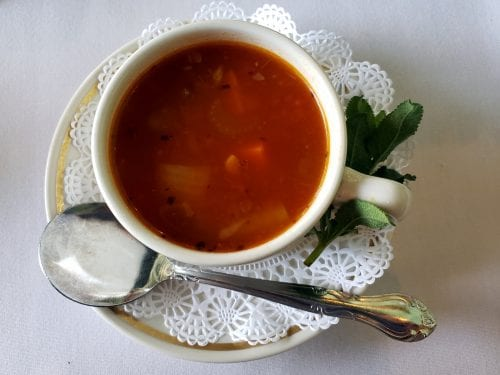 tomato-based vegetable soup in a white bowl