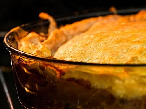 closeup of a meat pie baking in the oven