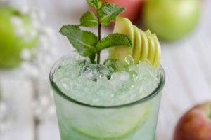 closeup of the top of a cocktail glass garnished with crushed ice, pear slices and a sprig of mint