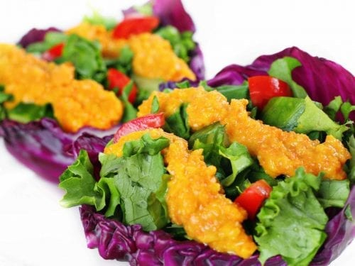 2 red lettuce salad cups covered in carrot miso dressing