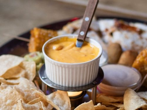 a small bowl of nacho cheese sauce surrounded by nacho chips and other finger foods