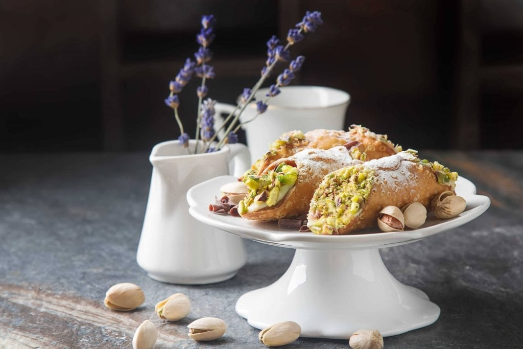 cannolis filled with ricotta cheese and pistachios on a white cake stand, with some lavender in a white vase in the background