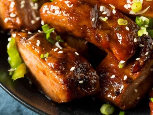 closeup bbq ribs garnished with chopped green onions and sesame seeds