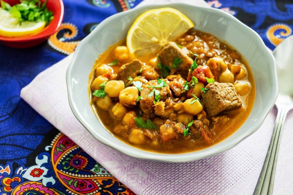 lentil stew with chickpeas and chunks of meat on a decorative ornate tablecloth