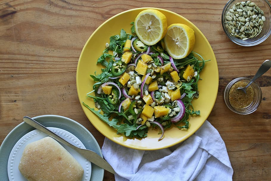 a plate of mango and goat cheese salad with 2 lemon halves on a yellow plate