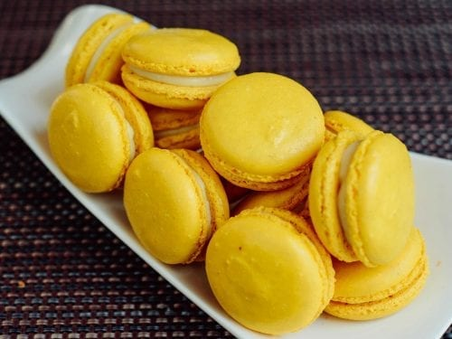 bright yellow macarons on a curved white plate