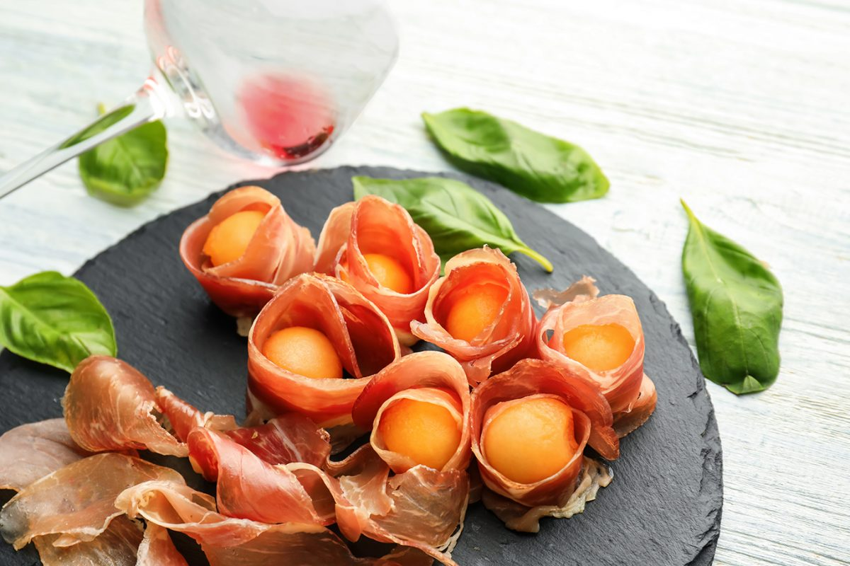 honeydew melon are wrapped in prosciutto and fresh mint