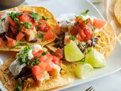round tortillas topped with beans, tomato and cheese