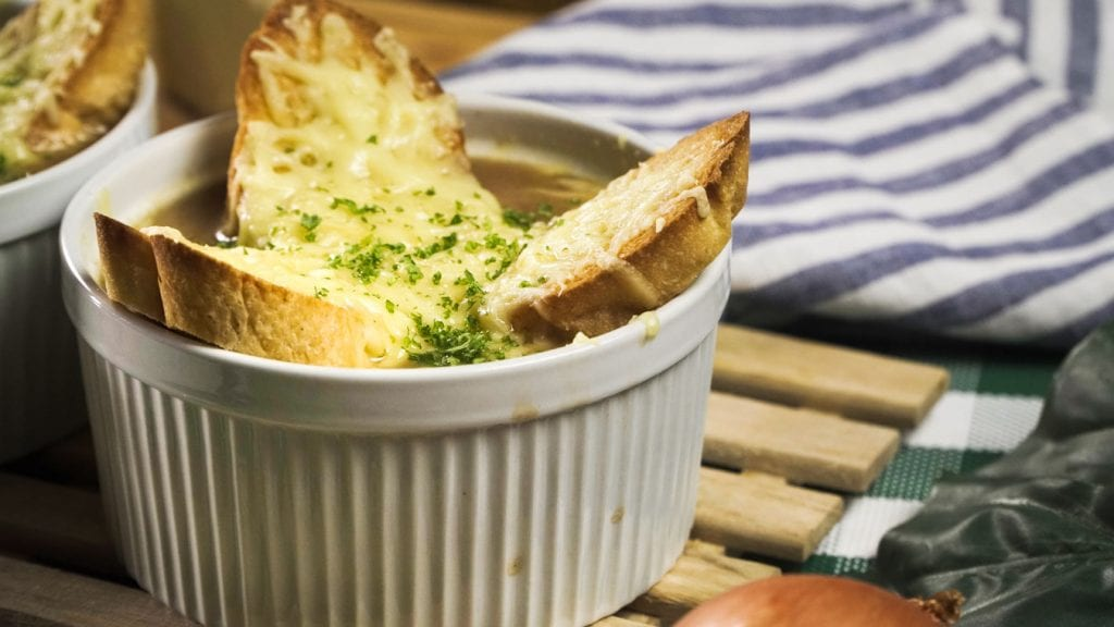 French Onion Soup Panera Copycat Recipe - Light soup made of caramelized onions and wine-infused beef broth with crispy baguette croutons and torched gruyere or emmental cheese on top on baked in the oven on a ramekin