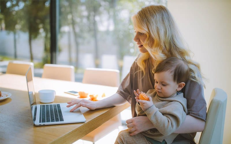 Working Mom on Laptop with Baby on Her Lap