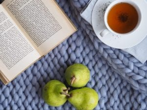 Chinese Tea: Surprising Benefits and 7 Famous Types to Try,a cup of tea with an open book and fruits.