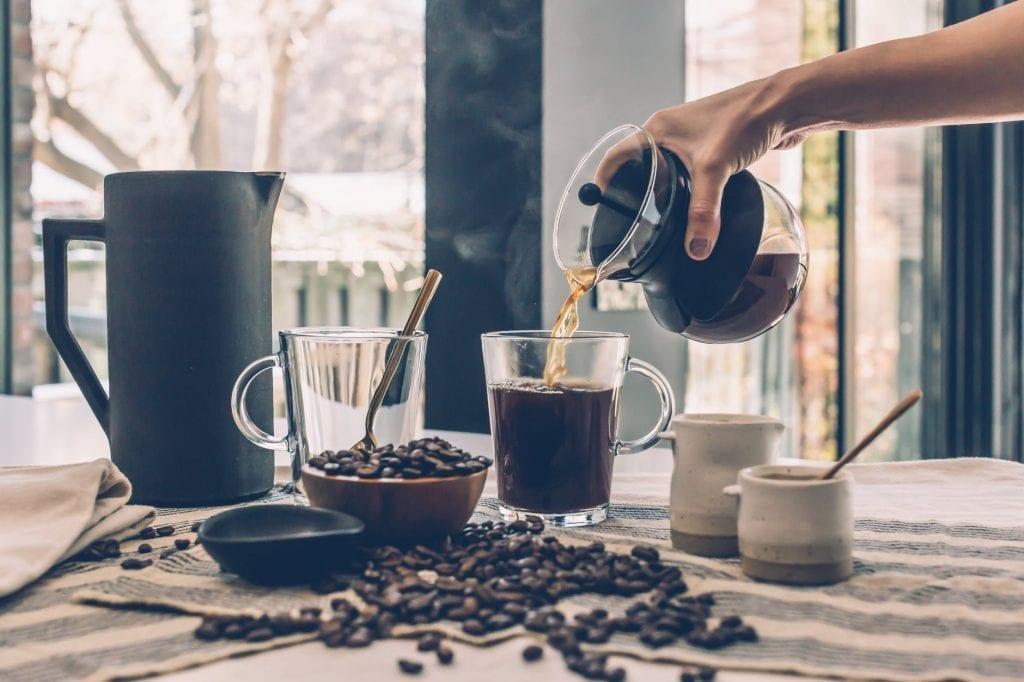 hand pouring over good morning coffee on a glass coffee mug