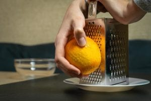 Person zesting an orange using a box grater