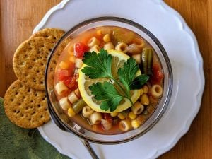 a top view of minestrone soup bowl garnished with lemon with biscuits on the side, pasta