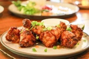Cooked chicken legs on a plate, garnished with scallions