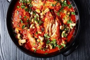 a top view of chicken cacciatore in a black dutch oven