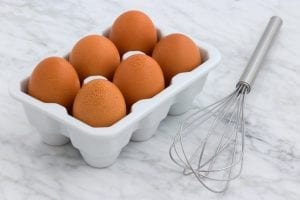 eggs inside a plastic egg tray with whisk on the side
