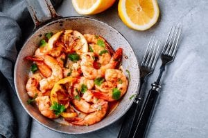Spicy garlic chilli Prawns Shrimps on frying pan with lemon and cilantro