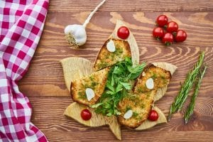 top view of Italian breads with garlic, tomatoes, and fresh herbs