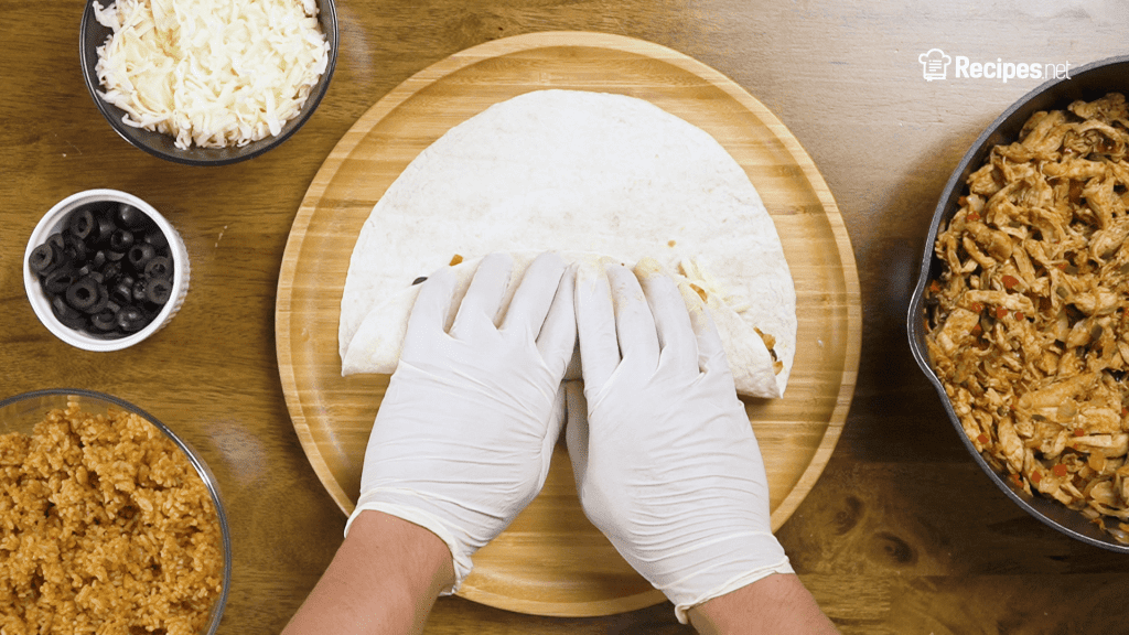 how to fold a burrito, step 2 of folding a burrito, hands gently rolling the tortilla wrap,