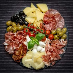top view of antipasto platter, italian dish, red meats, fresh fruits