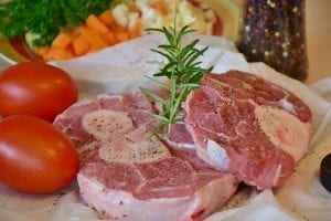 Raw pale meat with pepper, a rosemary sprig, and tomatoes.