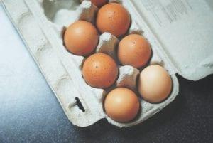 seven brown eggs inside an egg carton