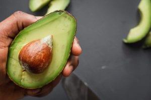 hand holding sliced avocado