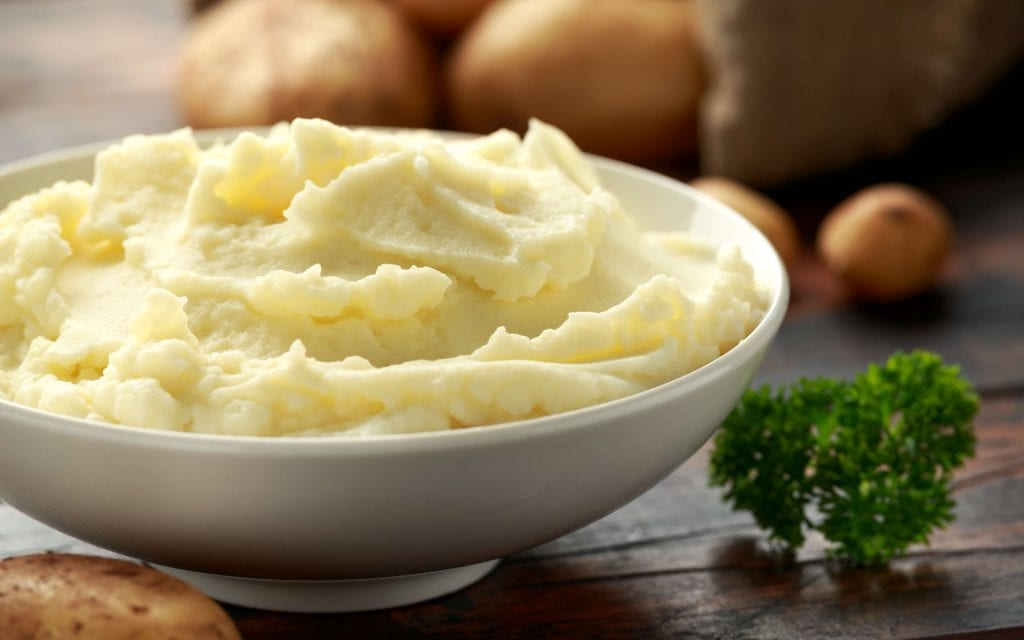 slow cooker mashed potatoes, mashed potatoes served on a saucer with leaves on side
