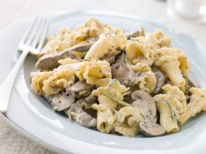 Plate of campanelle pasta noodles with mushrooms and vegetables in cream sauce