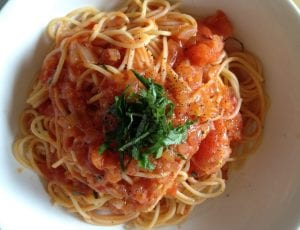 Bowl of capellini pasta in tomato sauce, with tomato chunks and herb garnish