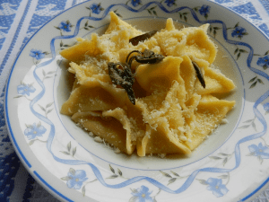 Plate of fagottini pasta garnished with grated cheese and herbs