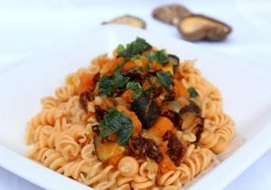 Fusilli pasta in red sauce, with chunks of grilled vegetables on top