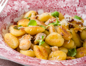 Bowl of gnocchi with cheese and herbs