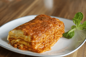 Lasagne or lasagna pasta casserole slices with meat, red sauce, bechamel, melted cheese, and garnished with greens