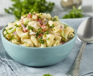Bowl of elbow macaroni or maccheroni pasta salad in cream sauce with bits of herbs and vegetables