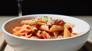 Bowl of penne pasta in tomato sauce, garnished with grated cheese and herbs